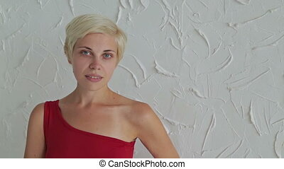 Pretty, young and blonde woman in red dress without make-up...