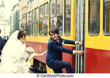 Bride tries to catch a groom who climbs on a tram