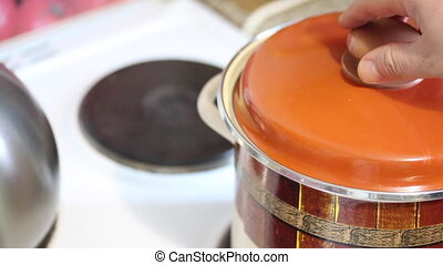 Preparation of carrot juice. The man opens the lid of the...