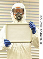 scientist in coverall,  goggles,mask,gloves holding blank whiteboard