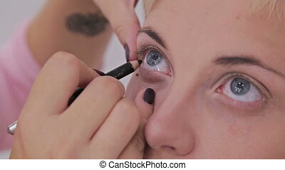 Professional make-up artist applying eyeliner around the...