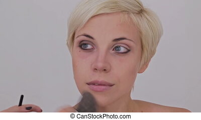Professional make-up artist applying powder to woman s face...