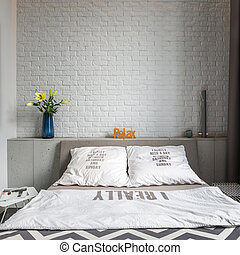 Cozy bedroom with double bed and white brick wall