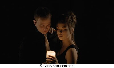 A loving couple, holding a candle, tenderly looking at each...