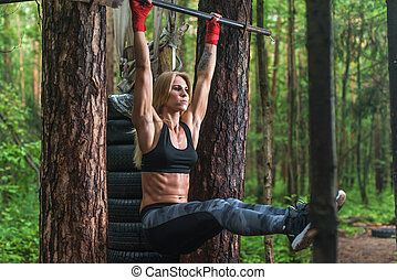 Fit woman doing hanging leg lifts abs muscles exercise on...