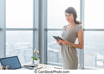 Businesswoman standing in loft light room, typing, reading...