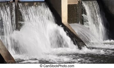 Water flowing ove a river dam - Flood waters flowing over...