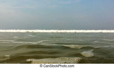 waves crash onto the coast and onto the camera,