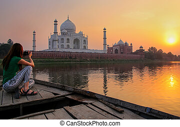 Woman watching sunset over Taj Mahal from a boat, Agra,...