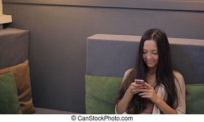 Young woman watches news of social networking on her smartphone.