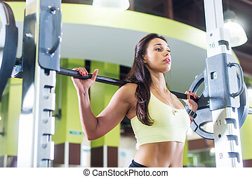 Fit woman doing squats with a barbell in Smith machine. -...