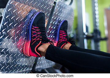 Close up shoes of a fit young woman doing leg press in the...