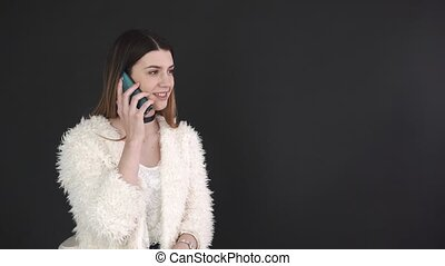 Beautiful girl talking on mobile phone against black background.