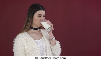 girl drinking a glass of milk on the red background.