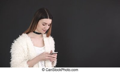 Young attractive woman using smart phone over grey...