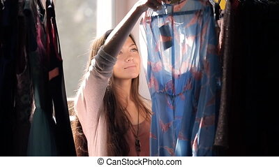 Brown-haired woman choosing dress from rack with hangers...