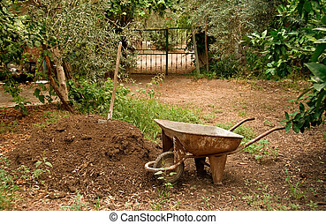 Wheel Barrow Next To Soil Heap - A wagon/wheelbarrow next to...