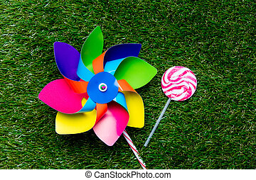 pinwheel toy and lollipop candy on green grass background,...