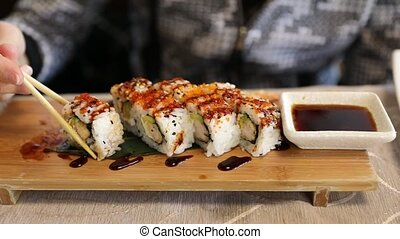 Tempura shrimp roll - Slow motion feeding on uramaki of...