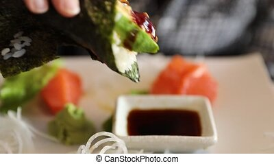 California Temaki Cone - Slow motion focus on hand eating a...