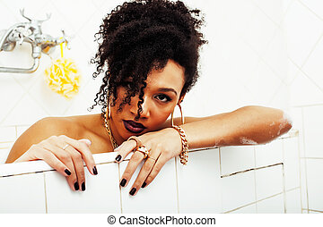 young afro-american teen girl laying in bath with foam,...