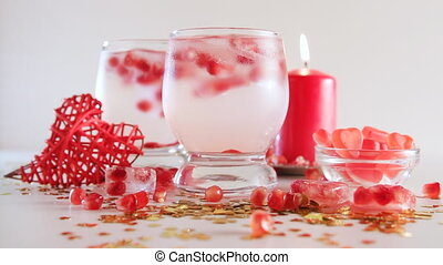 Seamless loop of romantic still life. Saint valentine's day celebration. Two glasses with alcoholic cocktail and ice, decorated with pomegranate, red candle, handmade heart and candies. Close-up.