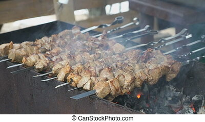 Meat are prepared on metal skewers on the coals - The cook...