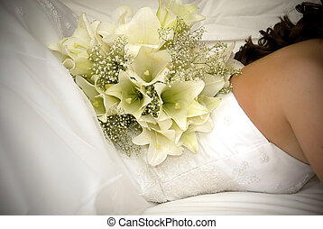 bride laying on bed with white flower bouquet on her back