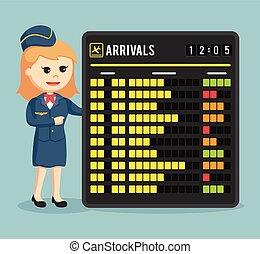 stewardess with arrivals schedule board