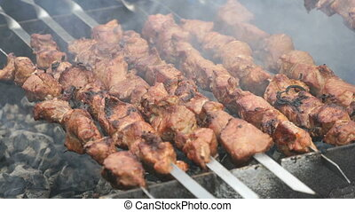 Cooking of pig meat on the metal skewers on coals outdoors....