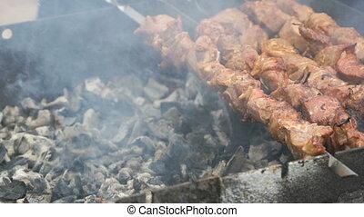 Cooking of pork skewers on metal skewers on coals outdoors....