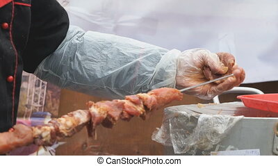 Male hand stringing pieces of raw meat on skewer for...