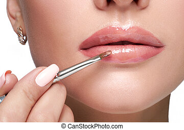 female paint her lips by cosmetic brush lipstick on lips -...