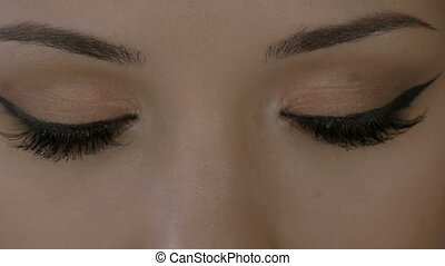 Young woman opens beautiful eyes. Close-up.