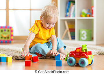 Kid toddler playing toy blocks in his room or nursery
