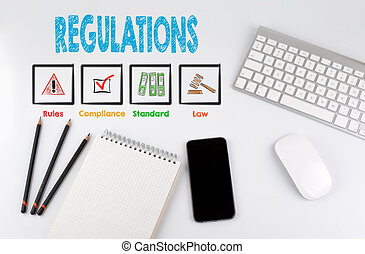 Regulations. Office desk table with computer, Smartphone, note pad, pencils