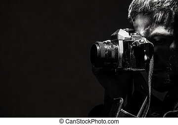 The young man photographs a retro old camera Black and white...