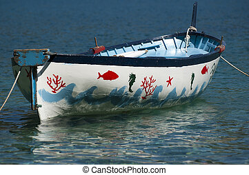 Old rowboat - An old colored rowboat anchored in the sea