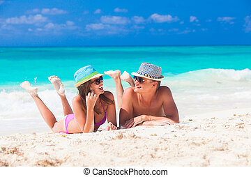 couple enjoying their time lying on sand at tropical beach -...
