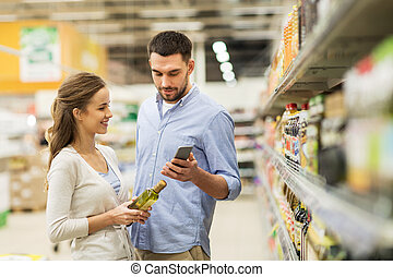 couple with smartphone buying olive oil at grocery -...