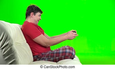 Man playing videogames with gamepad sitting on couch. Green...