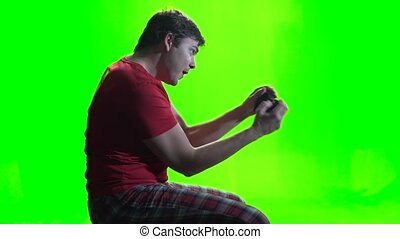 Gamer playing a new game on the gamepad. Green screen -...