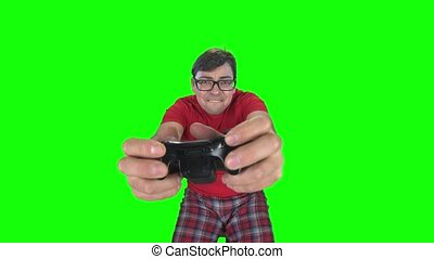 Bespectacled man makes faces playing on game console. Green...