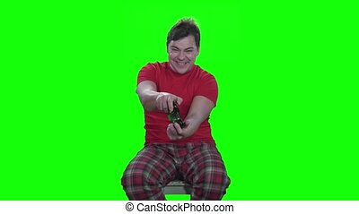 Green screen. Man emotionally plays on the gamepad