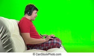 Gamer playing computer games sitting on the sofa. Green...