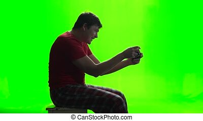 Green screen. Gamer playing a new game on the gamepad -...