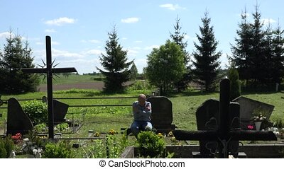 Despair mourning son man sit on bench near father grave in...