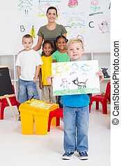 kindergarten boy holding his painting in front of classmates