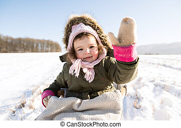 Cute little girl outside in winter nature, sitting on sledge...