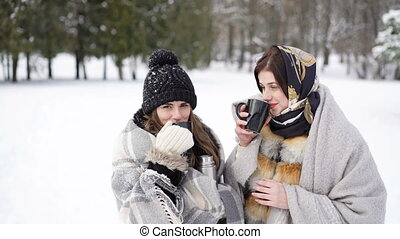 Two girls covered in warm plaid drinking hot tea in winter...